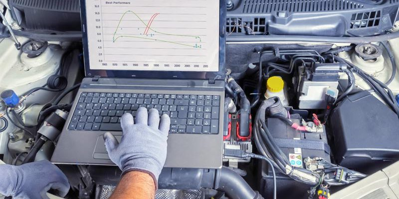 hand working on a computer resting on a car engine