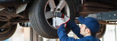 mechanic putting on a wheel on a car